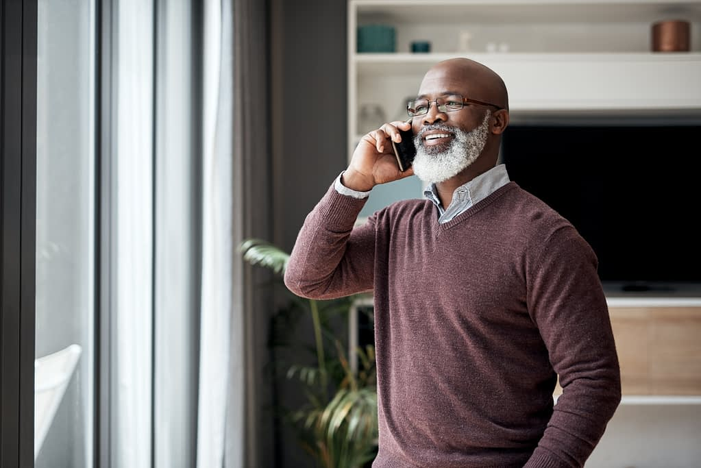 Older man speaking on his mobile phone from his living room.