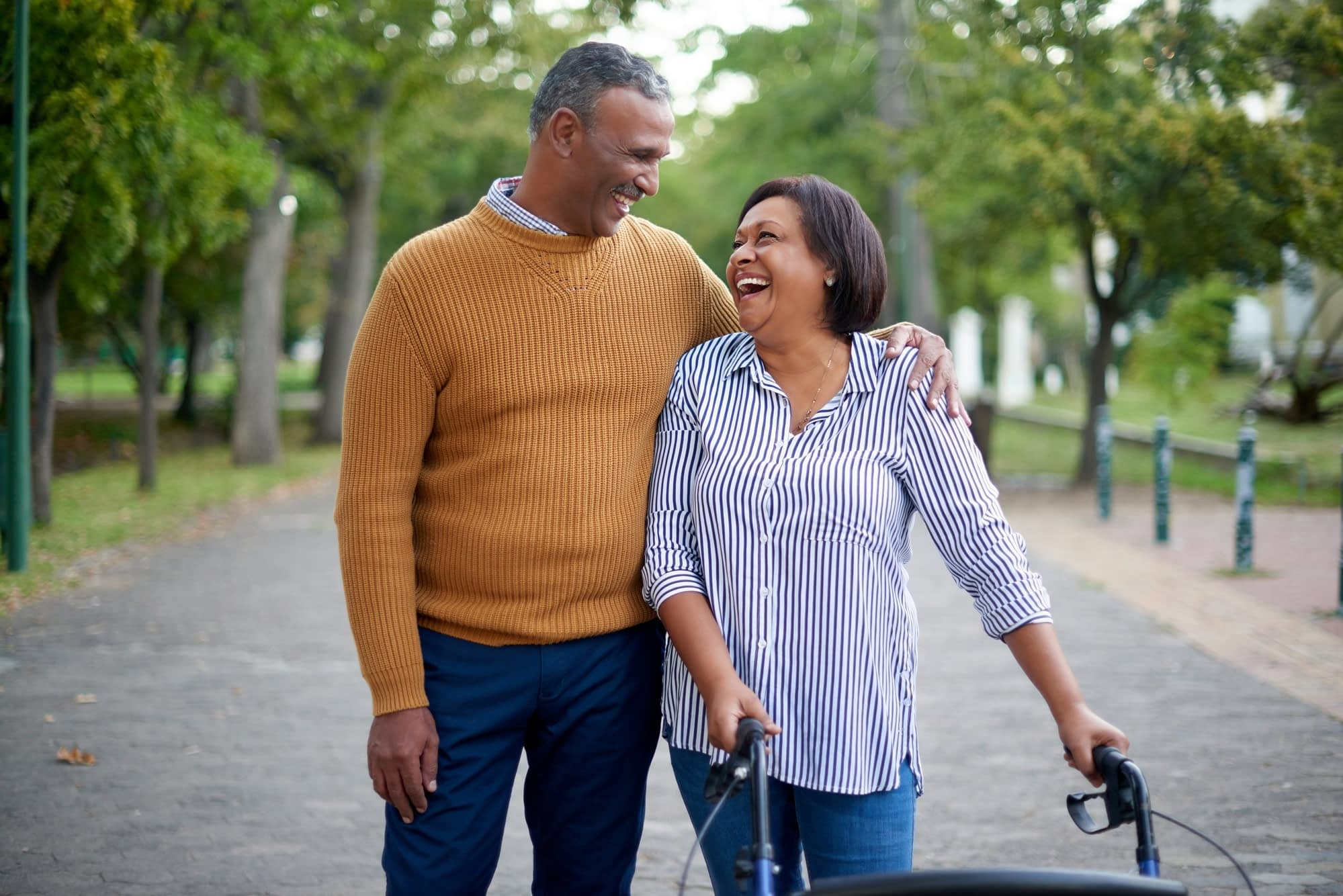 Happy middle-aged couple walking along path.
