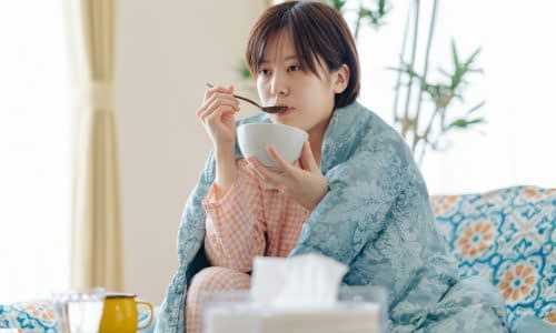 Sick woman eating a bowl of soup while recovering from illness