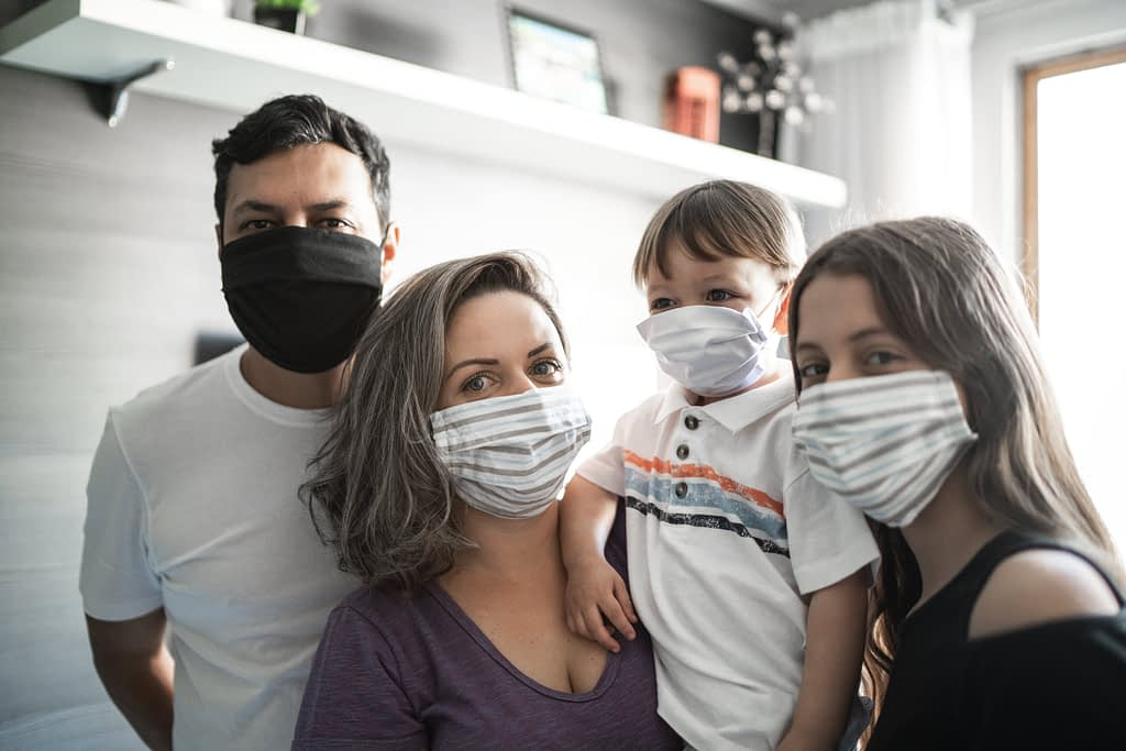 Young family gathered in their kitchen wearing face masks