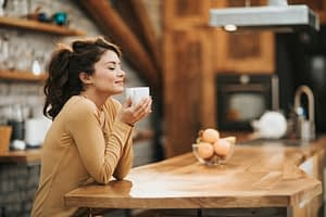 Young woman drinking a cup of coffee sitting at her kitchen table.