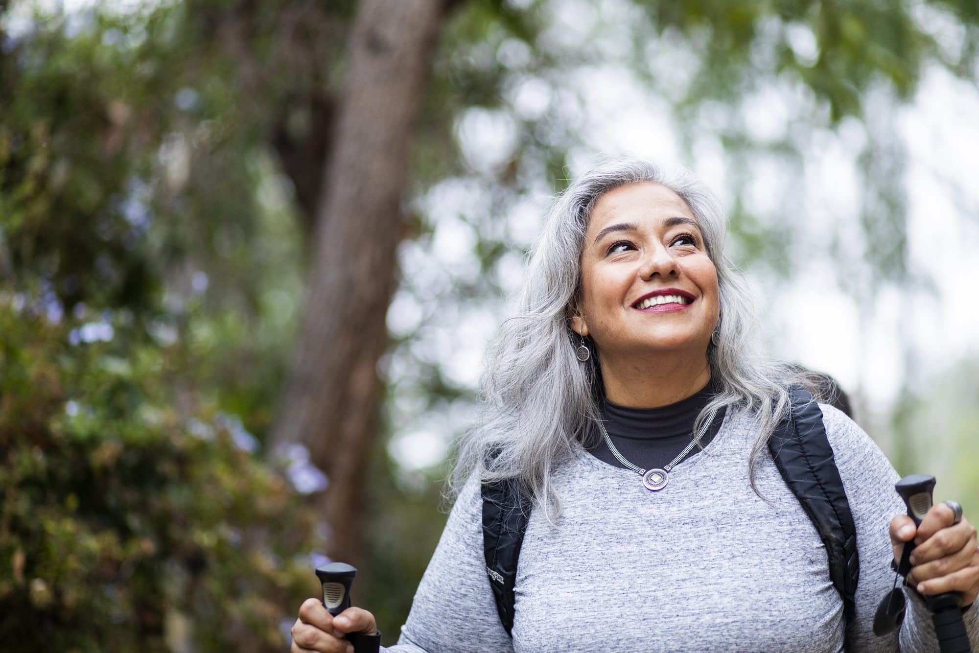 Woman out for walk in nature using walking sticks