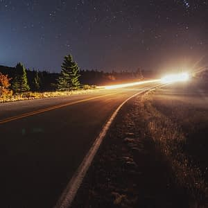 Car driving down a quiet road on a starry night